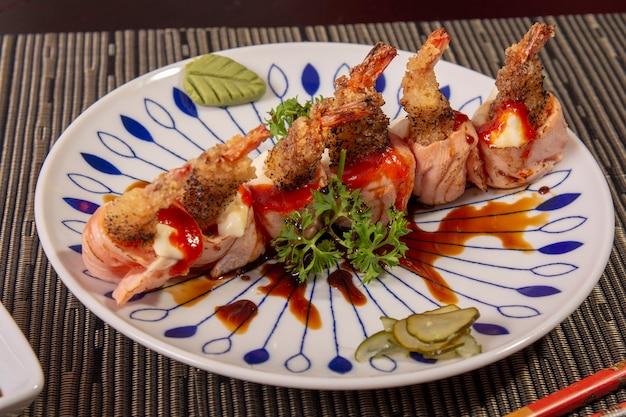 Cuisine asiatique, plat japonais aux crevettes et au saumon sushi avec légumes et sauce