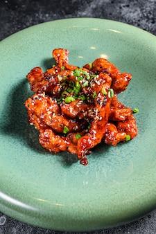 Cuisine asiatique: porc épicé dans une sauce aigre-douce. fond noir. vue de dessus