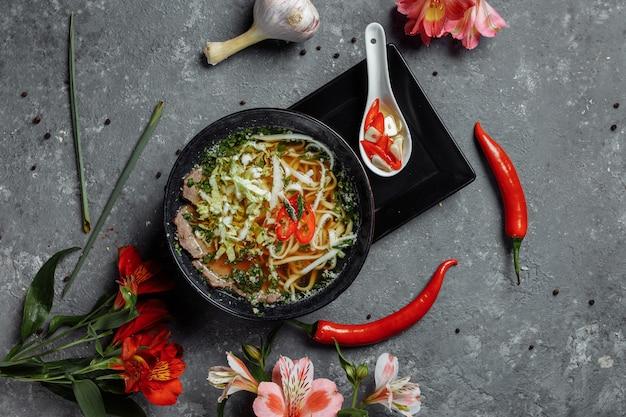 Cuisine asiatique, soupe de boeuf fo dans une assiette noire sur fond sombre