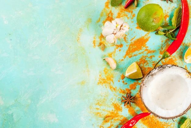 Cuisine asiatique et thaïlandaise, fond de cuisine. épices et ingrédients - noix de coco, gingembre, poivrons rouges chauds, citron vert, curry, menthe, épices.