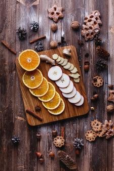 Cuisine au vin chaud. des oranges, des pommes et des espèces se trouvent sur une table en bois