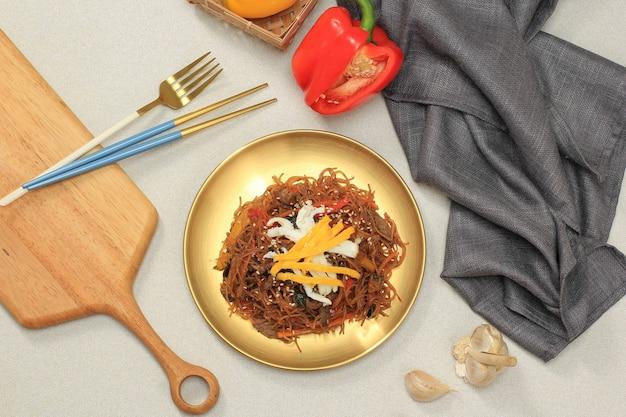 Cuisine authentique coréenne, japchae ou nouilles en verre sautées avec des légumes et de la viande dans une assiette dorée.