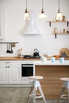 Cuisine blanche luxueuse et salon dans une grande maison