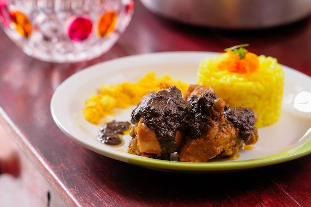 Cuisine brésilienne poulet à la sauce brune servi avec riz coloré