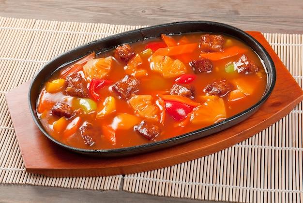 Cuisine chinoise. porc avec sauce sucrée acidulée, ananas et poivre