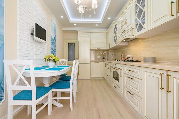 Cuisine classique contemporaine beige, blanche et cyan inrerior conçue dans le style provençal, tous les meubles avec portes et tiroirs ouverts