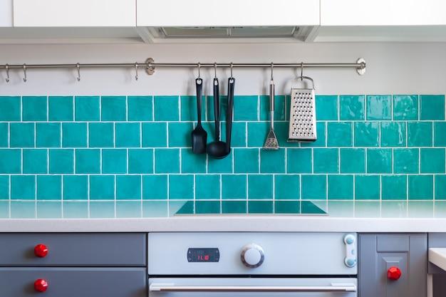 La cuisine comprend des armoires à devant plat gris foncé jumelées à des comptoirs en quartz blanc et à une tuile d'entretien bleu brillant.