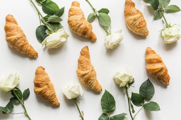 Cuisine créative et motif floral de croissants frais et de roses blanches. mise à plat.
