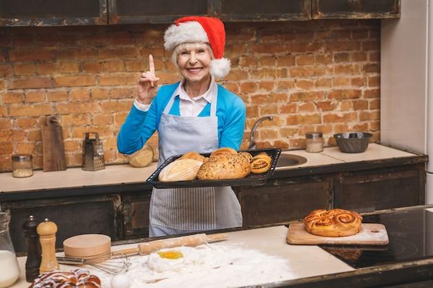 Cuisine du nouvel an. portrait de jolie femme âgée âgée cuisine sur cuisine. grand-mère faisant de savoureuses pâtisseries de noël.