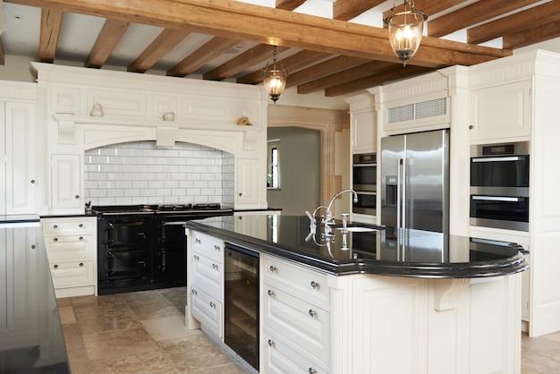 Cuisine équipée de luxe dans la maison avec plafond à poutres apparentes