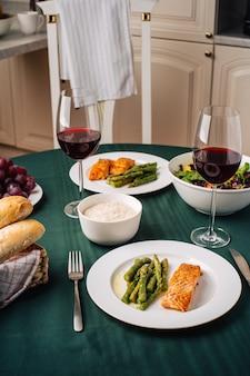 Cuisine européenne. pavé de saumon aux asperges, salade de légumes, sauce, raisins et pain avec verres de vin rouge. dîner pour deux dans la cuisine