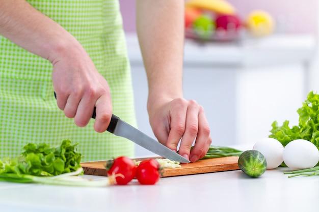 Cuisine femme en tablier hacher des produits écologiques pour une salade de légumes sains et frais dans la cuisine à la maison.