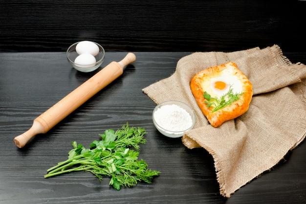 Cuisine géorgienne. khachapuri sur un sac, de la farine, des œufs et un rouleau à pâtisserie. table noire. espace pour le texte