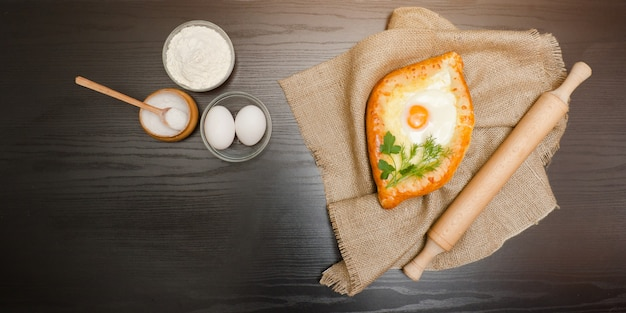 Cuisine géorgienne, vue de dessus de khachapuri sur un sac, de la farine, des œufs et du rouleau à pâtisserie.