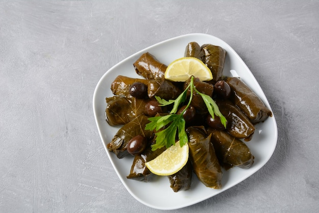 Cuisine grecque traditionnelle. riz enveloppé dans des feuilles de vigne. dolma au citron, épices, diverses olives marinées et piments forts.