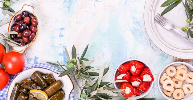 Cuisine grecque traditionnelle. riz enveloppé dans des feuilles de vigne. dolma au citron, épices, olives au vinaigre et piments forts. branches fraîches et plats faits maison