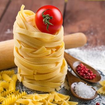 Cuisine italienne - différentes pâtes avec des ingrédients sur une table en bois.