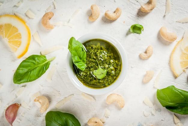 Cuisine italienne et méditerranéenne sauce au pesto avec des ingrédients sur une table en pierre blanche: parmesan fromage noix de cajou beurre citron basilic