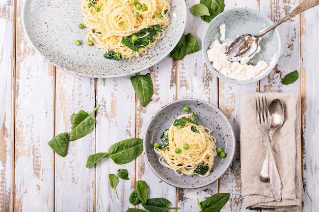 Cuisine italienne: pâtes fraîches aux oeufs végétariens tagliatelles carbonara servi avec du fromage ricotta et des épinards sur fond de bois blanc