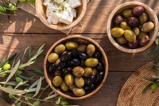Cuisine italienne, avec poivrons et olives vertes, farcies de fromage, olives noires, huile d'olive sur table en bois