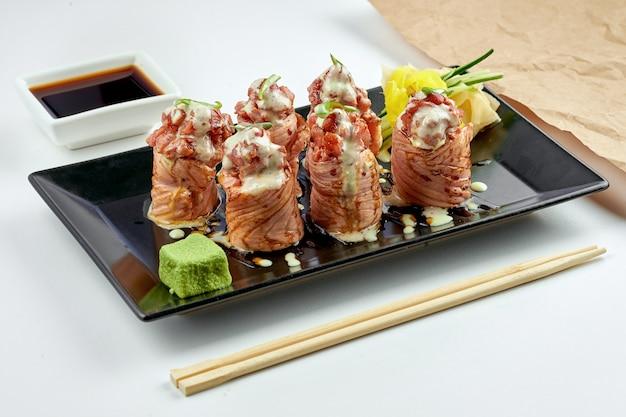 Cuisine japonaise classique - rouleau de sushi de philadelphie avec thon épicé, saumon frit, sauce blanche, servi dans une assiette noire. sur une surface blanche.