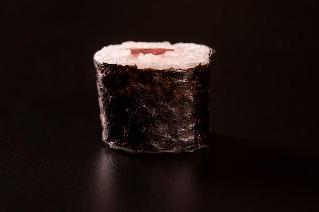 Cuisine japonaise. une paix de sushi roll isolé sur fond noir gros plan tourné