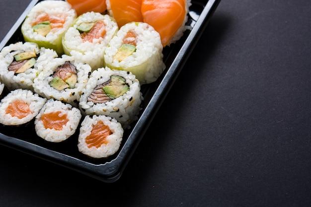 Cuisine japonaise: sushis maki et nigiri sur fond noir, espace copie