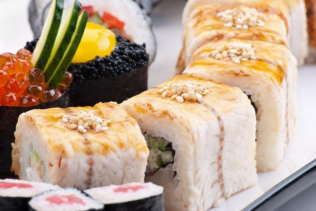 Cuisine japonaise traditionnelle sushi. sushi japonais gros plan sur une plaque blanche. ensemble de sushis
