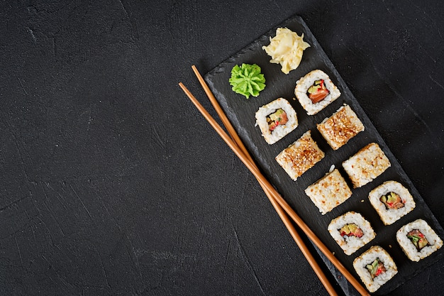 Cuisine japonaise traditionnelle - sushis, petits pains et baguettes pour les sushis sur un fond sombre. vue de dessus