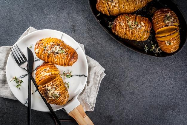 Cuisine maison traditionnelle américaine. le régime végétalien. pomme de terre hasselback maison avec des herbes fraîches et du fromage.