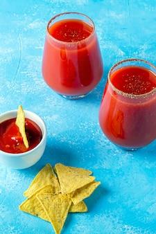 Cuisine mexicaine traditionnelle: nachos, chips tortilla de maïs avec sauce épicée et boisson alcoolisée michelada