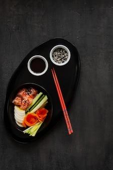 Cuisine à la mode asiatique colorée, bol à sushis avec concombre, saumon, carotte, avocat