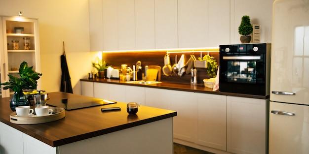 Cuisine moderne et technologique dans une nouvelle maison de luxe avec îlot en bois