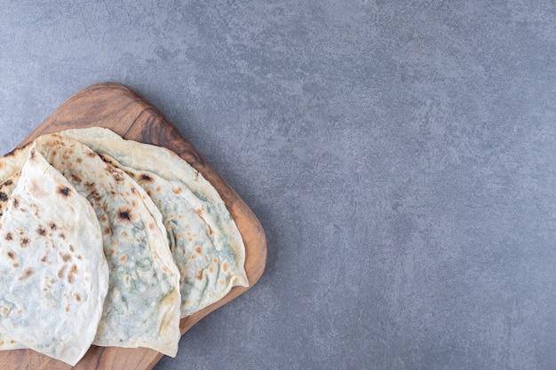 Cuisine nationale azerbaïdjanaise. gutab, sur une planche à découper sur une table en marbre.