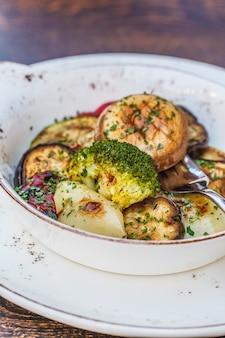 Cuisine nationale des balkans: légumes grillés dans une assiette blanche sur la table du restaurant