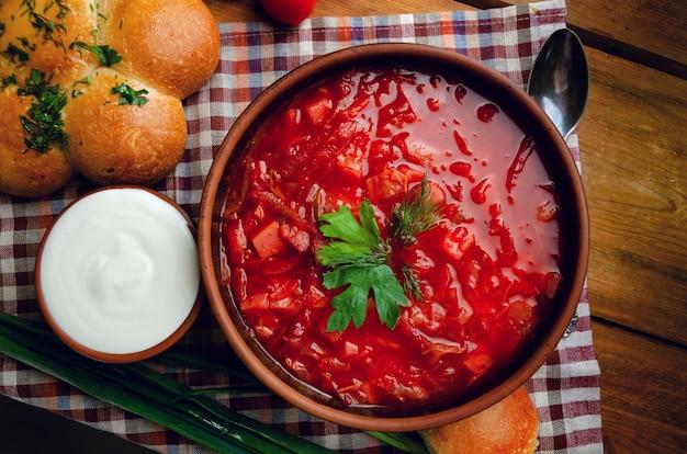 Cuisine nationale ukrainienne - bortsch rouge avec des beignets dans un bol en argile sur une table en bois.