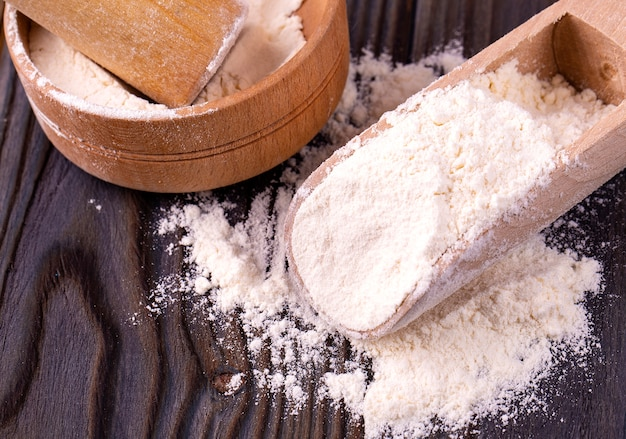 Cuisine nature morte avec de la farine sur la table en bois. fermer.