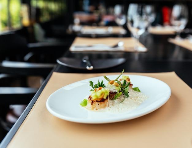 Cuisine raffinée créative: pétoncles d'hokkaido au velouté de pomme verte, de noisette et de coquillages.