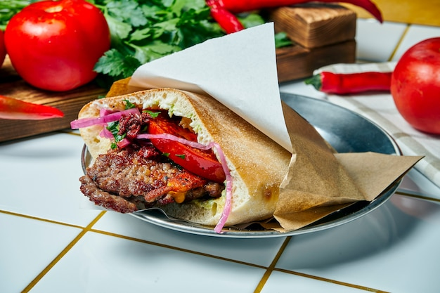 Cuisine de rue savoureuse - pita avec tomate, oignon et sauce, burger de boeuf sur un tableau blanc. cuisine grecque. vue.