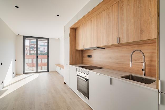 Cuisine et salon minimalistes contemporains avec balcon dans un appartement rénové vide meublé en bois ...