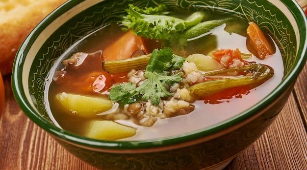Cuisine tadjike de brinchoba, soupe aux légumes et riz, assortiment de plats tadjiks traditionnels, vue de dessus.