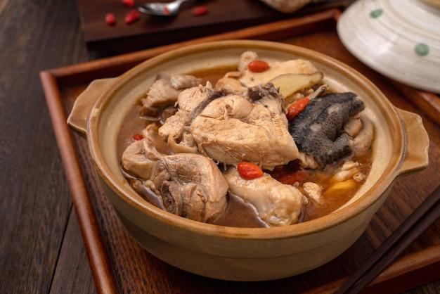 Cuisine taïwanaise - délicieuse soupe de poulet à l'huile de sésame maison dans un bol sur fond de table en bois foncé.
