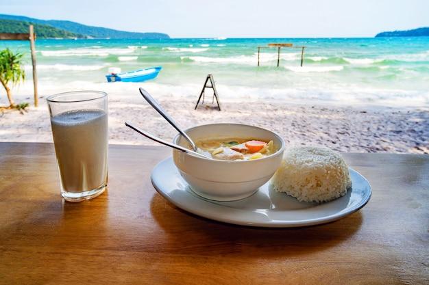 La cuisine thai. une assiette de soupe avec du lait de coco et du riz bouilli sur la table contre le magnifique paysage marin. petit déjeuner au restaurant de la plage. côte de l'île de koh rong samloem, cambodge.