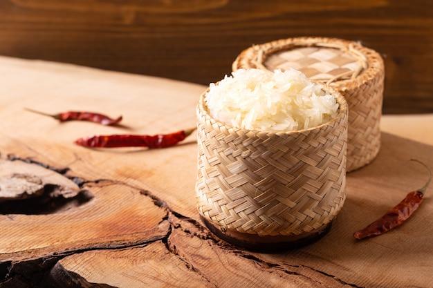 Cuisine thaïlandaise asiatique riz gluant ou gluant en osier de bambou sur fond en bois avec espace de copie