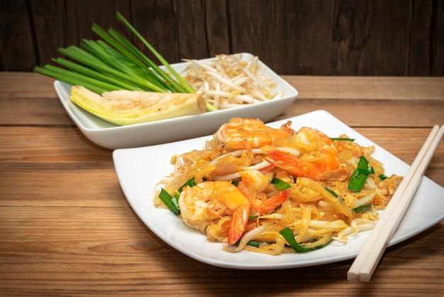 Cuisine thaïlandaise célèbre appelée pad thai sur une plaque blanche