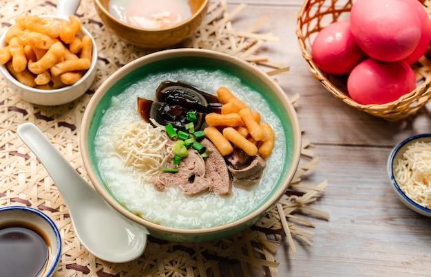 Cuisine thaïlandaise congee de riz avec des tranches d'œufs du siècle tranchés de foie bouillant et de pâte croustillante frite avec garniture de nouilles croustillantes et de sauce soja