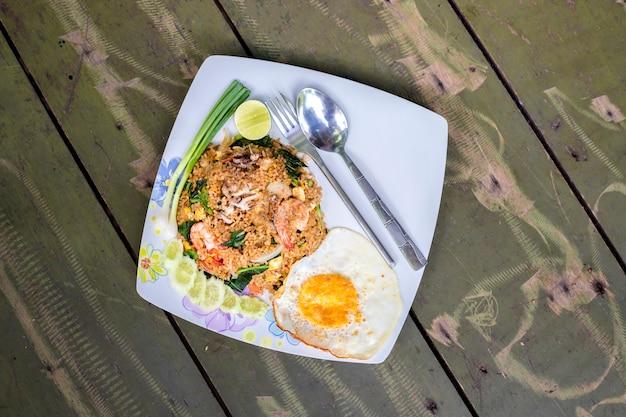 Cuisine thaïlandaise, fruits de mer de riz frit, crevettes, calmars et oeufs frits sur fond de bois