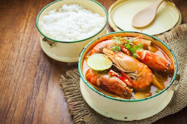 Cuisine thaïlandaise, soupe épicée de crevettes de rivière ou tom yum goong sur table en bois