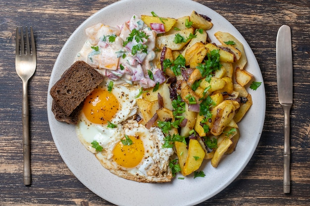 Cuisine ukrainienne traditionnelle, pommes de terre frites aux oignons, œufs au plat, salade de légumes, pain noir sur fond de bois, gros plan, vue du dessus