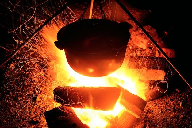 Cuisiner sur le bûcher la nuit. grande flamme